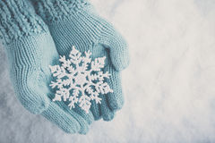 Female hands in light teal knitted mittens with sparkling wonderful snowflake on  white snow background. Winter, Christmas concept Stock Photo