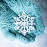 Female hands in light teal knitted mittens with sparkling wonderful snowflake on white snow background. Winter, Christmas concept Stock Image