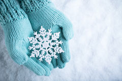 Female hands in light teal knitted mittens with sparkling wonderful snowflake on white snow background. Winter, Christmas concept
