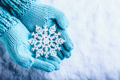 Female hands in light teal knitted mittens with sparkling wonderful snowflake on a white snow background. Winter Christmas concept. Female hands in light teal