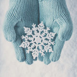 Female hands in light teal knitted mittens with sparkling wonderful snowflake on  white snow background. Winter, Christmas concept Royalty Free Stock Images