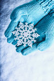 Female hands in light teal knitted mittens with sparkling wonderful snowflake on a white snow background. Winter Christmas concept Stock Photography