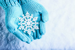 Female hands in light teal knitted mittens with sparkling wonderful snowflake on a white snow background. Winter Christmas concept Royalty Free Stock Image