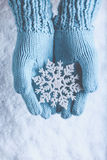 Female hands in light teal knitted mittens with sparkling wonderful snowflake on a white snow. Winter and Christmas concept.