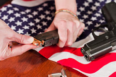 Second amendment concept. Female hands loading a hand gun with hallow point bullets and an american flag in the background Royalty Free Stock Images