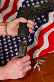 Second amendment concept. Female hands loading a hand gun with hallow point bullets and an american flag in the background Royalty Free Stock Photos