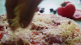 Female hands make a pizza on a wooden board are the ingredients for the pizza: tomatoes, cheese, basilic, olives stock video