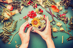 Female hands making autumn flowers arrangements in vase Royalty Free Stock Photography