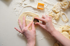 Female hands making cookies from fresh dough. Close up of female hands making cookies from fresh dough at home. dough, flour, baking tins on a white table in the Stock Image
