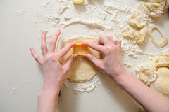 Female hands making cookies from fresh dough. Close up of female hands making cookies from fresh dough at home. dough, flour, baking tins on a white table in the Royalty Free Stock Photo