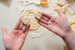 Female hands making cookies from fresh dough. Close up of female hands making cookies from fresh dough at home. dough, flour, baking tins on a white table in the Stock Photos