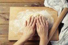 Female Hands Making Dough for baking pie, or pizza. Homemade Preparing Food. Top view. Rustic background. Female Hands Making Dough for baking pie, or pizza stock images