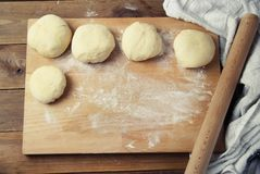 Female Hands Making Dough for baking pie, or pizza. Homemade Preparing Food. Top view. Rustic background. stock photos