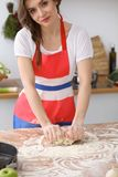 Female hands making dough for pizza or bread on wooden table. Baking concept Royalty Free Stock Images