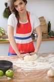 Female hands making dough for pizza or bread on wooden table. Baking concept Stock Image