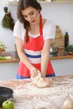 Female hands making dough for pizza or bread on wooden table. Baking concept Royalty Free Stock Photo