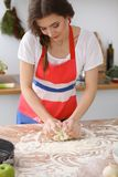 Female hands making dough for pizza or bread on wooden table. Baking concept Stock Photos