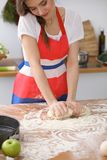 Female hands making dough for pizza or bread on wooden table. Baking concept Stock Images