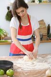 Female hands making dough for pizza or bread on wooden table. Baking concept Stock Photo