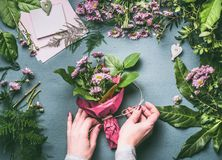 Female hands making flowers bouquet arrangement with green leaves decoration on working gray table with florist tools and accessor. Ies, top view, step by step Stock Photo