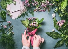 Female hands making flowers bouquet arrangement on working gray table with florist tools and accessories. Top view, step by step Royalty Free Stock Photo