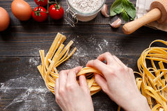 Female hands making fresh homemade pasta. Pasta ingredients on the dark wooden table top view Stock Photos