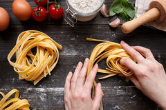 Female hands making fresh homemade pasta. Pasta ingredients on the dark wooden table top view Royalty Free Stock Photos
