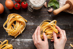 Female hands making fresh homemade pasta. Pasta ingredients on the dark wooden table top view Stock Photo