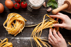 Female hands making fresh homemade pasta. Pasta ingredients on the dark wooden table top view Stock Images