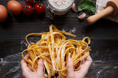 Female hands making fresh homemade pasta. Pasta ingredients on the dark wooden table top view Stock Photography