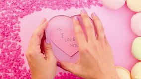 Female hands making a love present to girlfriend with I love you sign sticker. Female hands making a golden ring love present to girlfriend / boyfriend with I stock footage