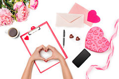 The female hands making heart and gift box with hearts on white background. The female hands making heart, gift box, ribbon, hearts and blank sheet of paper and royalty free stock image