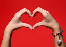 Female hands making a heart shape over red Stock Photos
