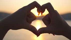 Female hands making heart shape over sea background with beautiful golden sunset. Concept of summer vacation. Close up. Slow motion stock video