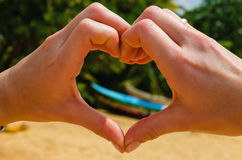 Female hands making heart shape by the sea Stock Photo