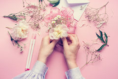 Female hands making lovely floral arrangement with flowers and ribbon on pale pink background, top view. Creative greeting, Invita Royalty Free Stock Photography