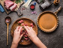 Female hands making minced meat stuffing on kitchen table background with meat, force meat , meat grinder and spoon, top view. Co stock image
