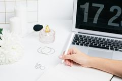 Female hands making notes in a notepad on a white table with a laptop keyboard stock photos