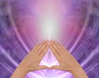 Working with Pyramid Healing Energy. Female hands making a triangle shape on a magenta purple flowing triangular shaped energy field with plenty of copy space Stock Photos