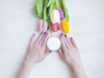 Female hands manicure, above treatment cosmetic cream, tulip flower on wooden background royalty free stock photos