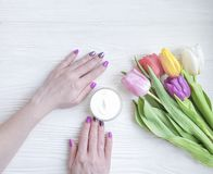 Female hands manicure, cosmetic cream, tulip flower on wooden background stock photography