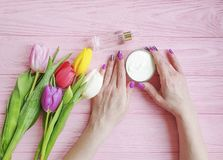 Female hands manicure, above treatment elegant cosmetic cream, natural tulip flower on wooden background stock images