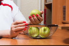 Female hands with manicure get apples from a basket stock image