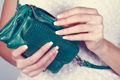 Female hands with manicure with green handbag Stock Images