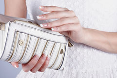 Female hands with manicure with handbag. Beautiful female hands with manicure hold an open white handbag Royalty Free Stock Images
