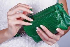 Female hands with manicure with handbag. Beautiful female hands with manicure hold an open green handbag Royalty Free Stock Photos
