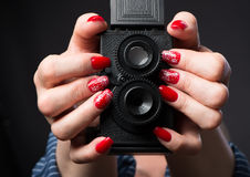 Female hands with manicure hold a camera. Female hands with manicure hold a model of a two-objective camera Royalty Free Stock Photography