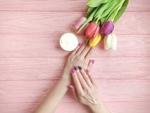 Female hands manicure, lotion above summer treatment elegant cosmetic cream, natural tulip flower on wooden stock photo