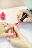 Female hands manicure woman by nail polish Stock Photo