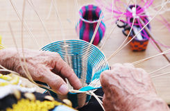 Female hands manually weaving bamboo basket Royalty Free Stock Images